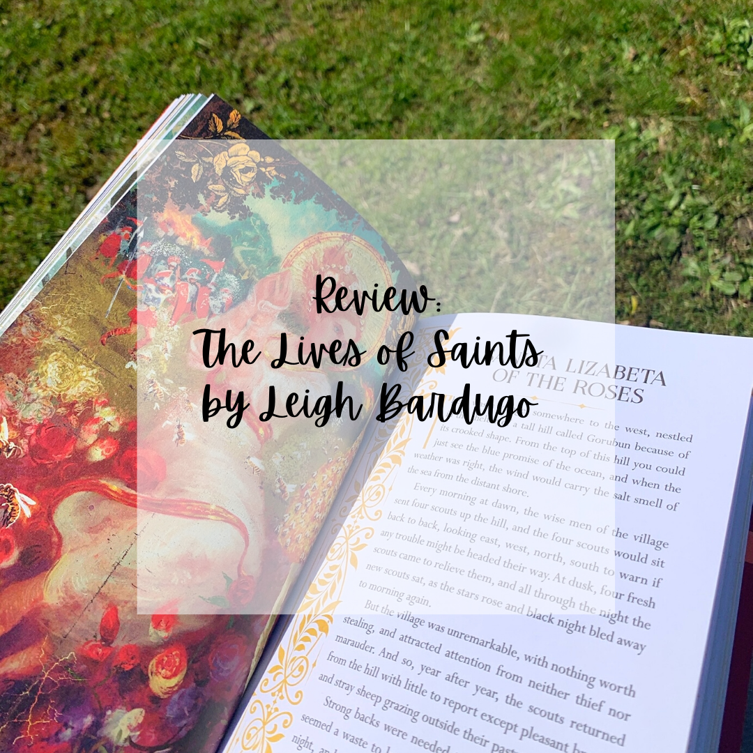 "Text reads ""Review: The Lives of Saints"" by Leigh Bardugo"" over a photo of the open book"